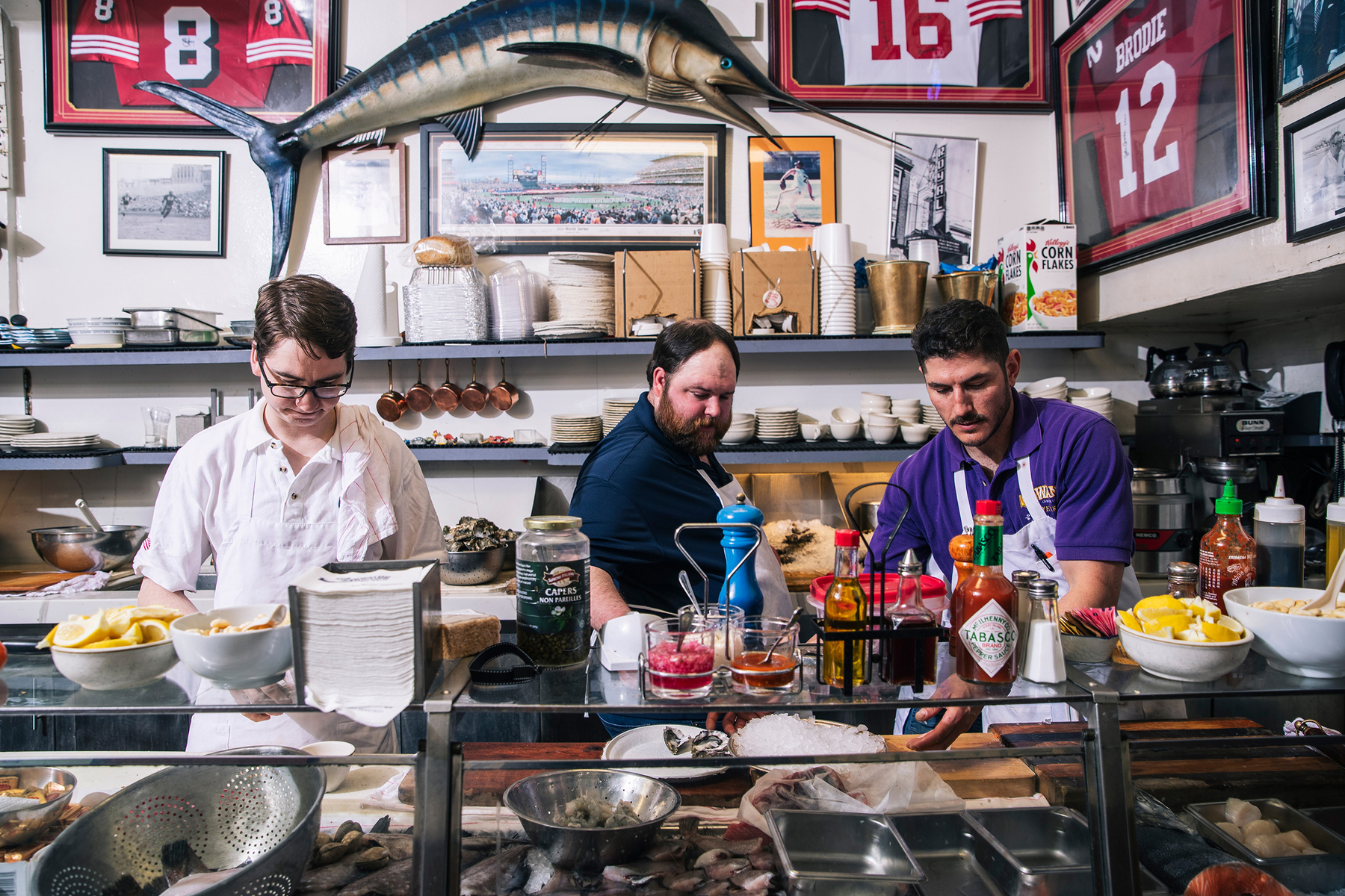 From left, Brian Dwyer, Erik Wideman, and Marino Peradotto prepares seafood before service at Swan Oyster Depot in San Francisco, Calif. on Tuesday, April 2, 2019.