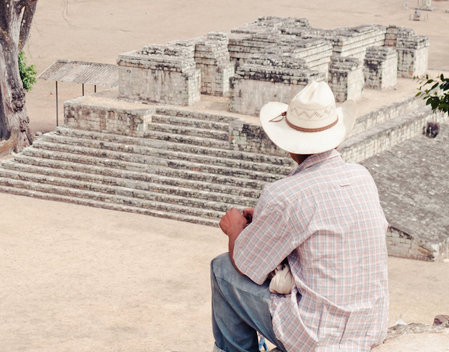 Honduran man looking out on a Mayan temple in Copan Ruinas, Honduras