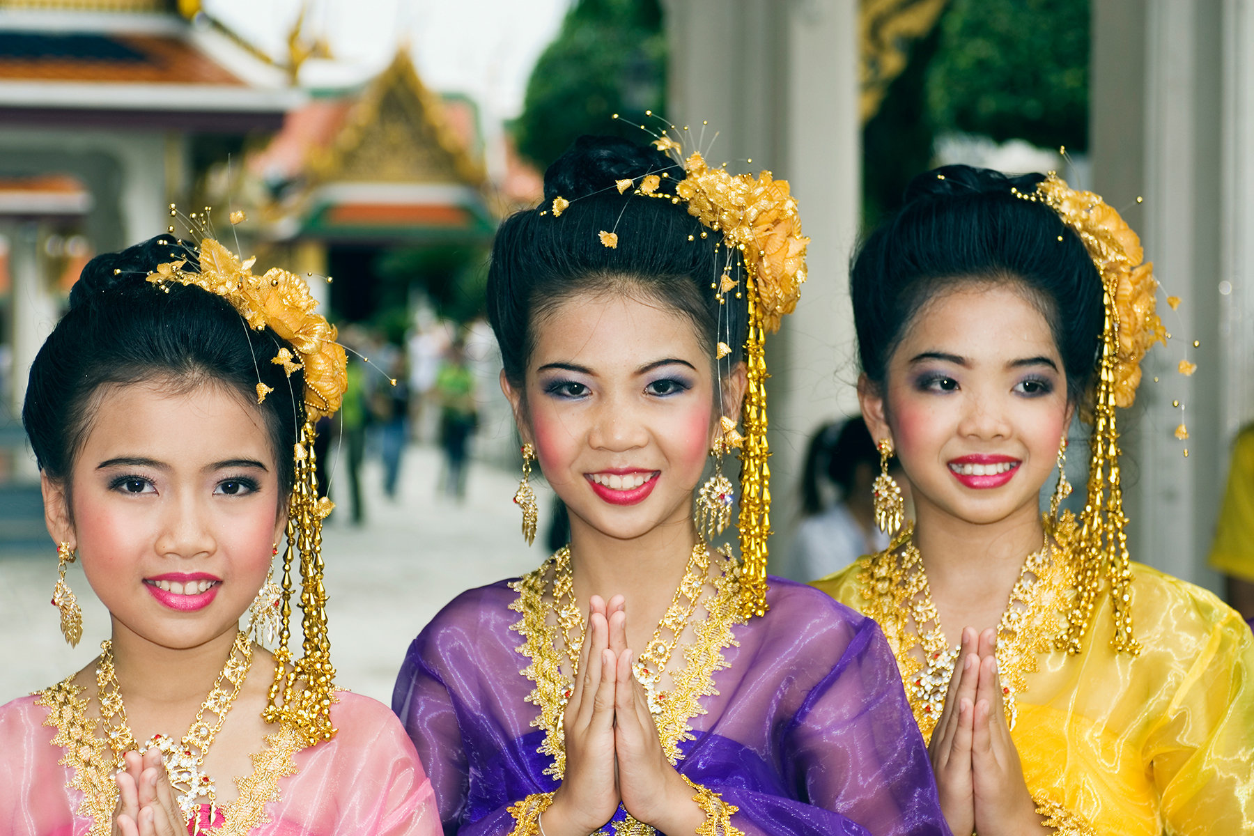 Thailand, Bangkok, Royal Palace, Girls dressed In traditional Thai clothing greeting visitors and tourists