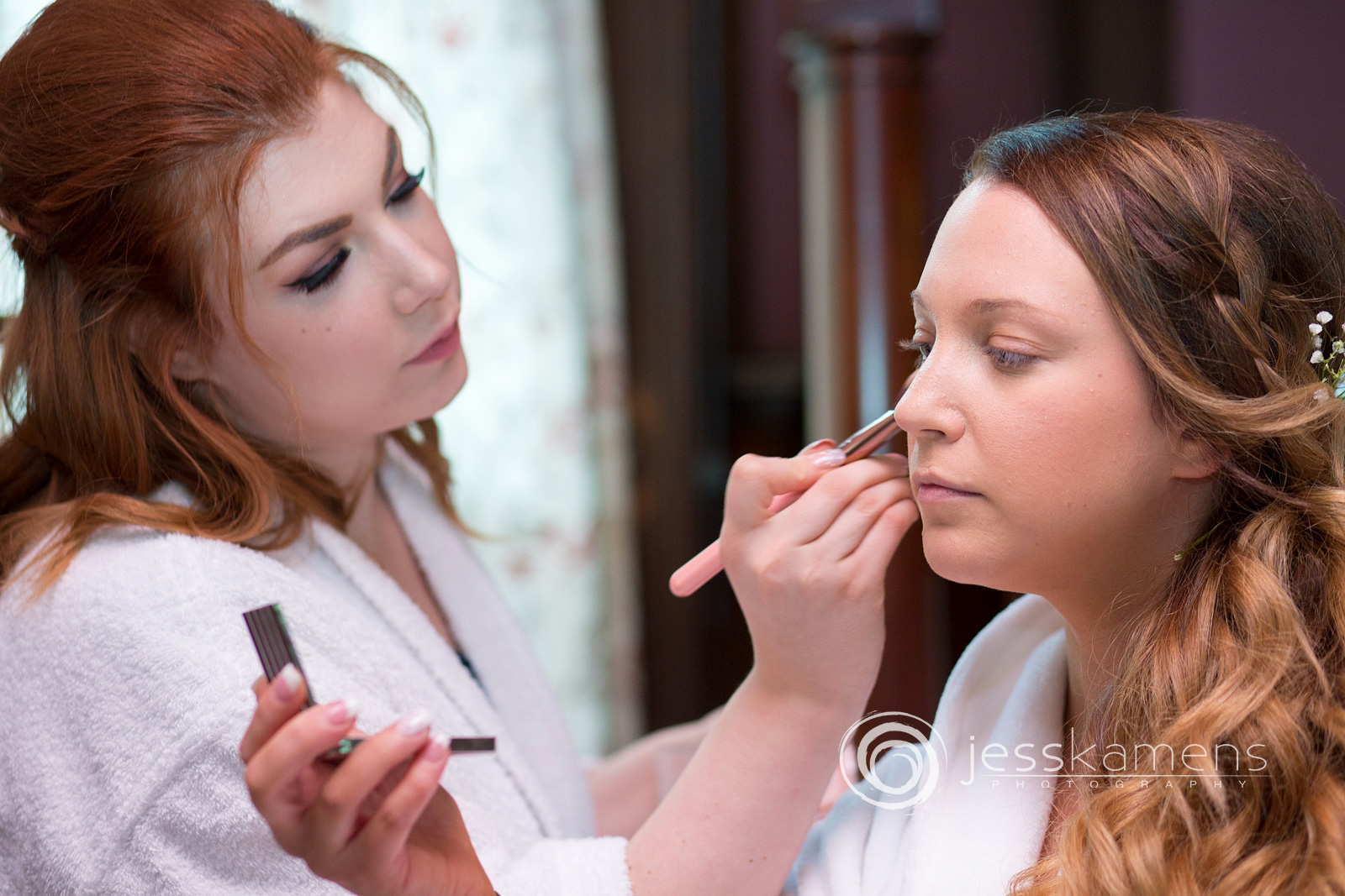 bride is getting her makeup done on her wedding day