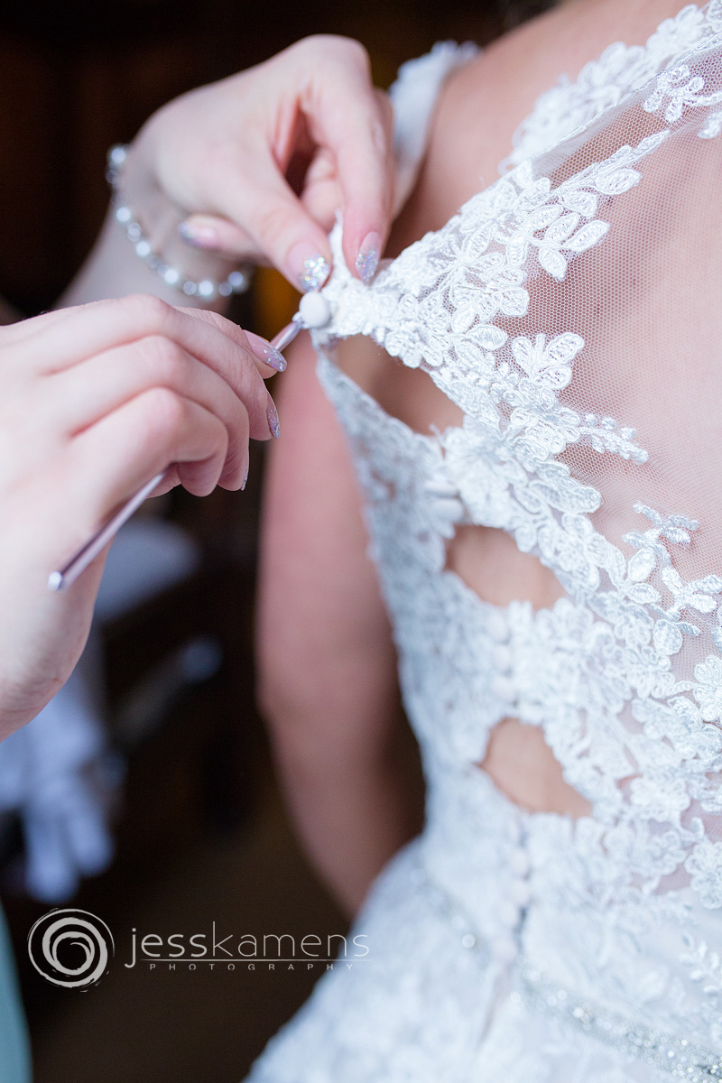 a bride's dress gets buttoned up and hooked from the back.
