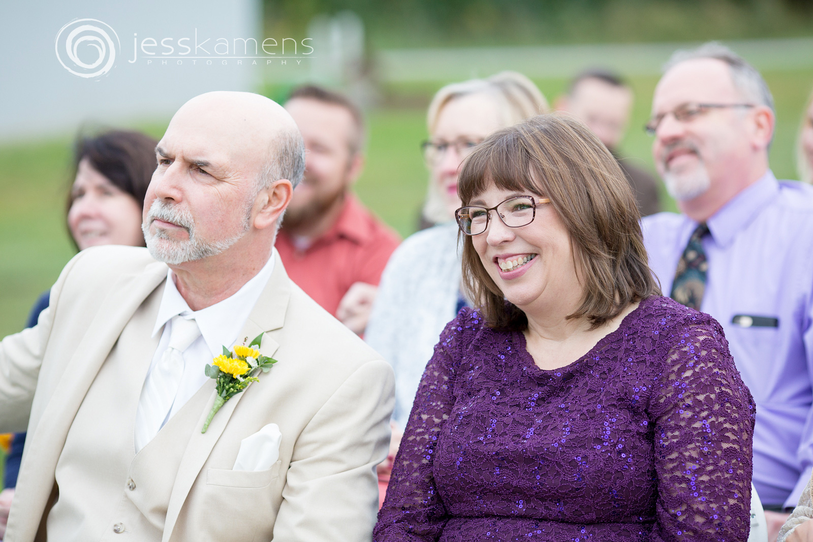 parents of the new husband and wife laugh during a joke in a wedding ceremony