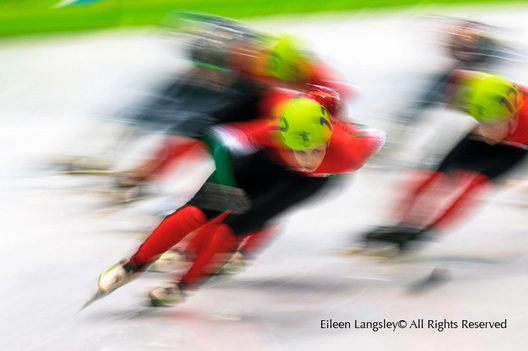 A slow motion blurred action image from the short track speed skating event.