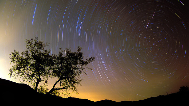 A time exposure captures the stars streaking around the north star- with rogue meteorites wildly dashing thru the sky.