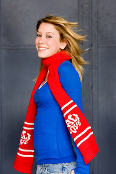 Teen girl smiling in red scarf and blue sweater, her blonde hair blows.