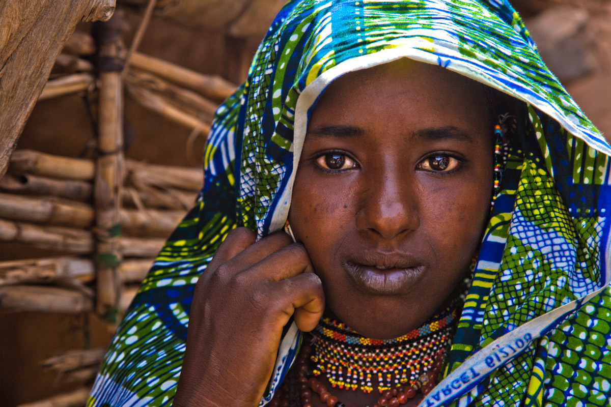 This Fulani woman has walked to Torodi from a village ten miles away to attend the weekly market.  She wears her brightest newest clothing to show off on market day, together with her bead chokers and beaded earrings.  Her jewelry is handmade and can take days to make.