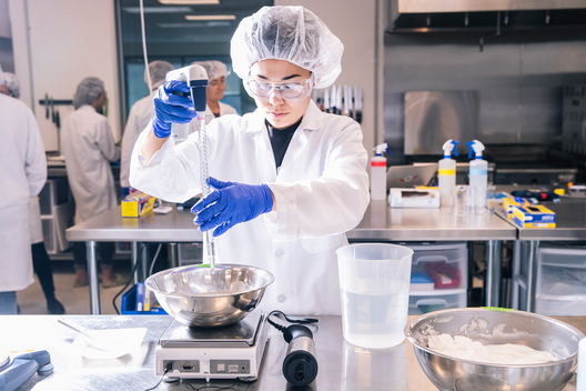 A technician measures an ingredient with a pipette at the test kitchen inside Impossible Foods headquarters in Redwood City, Calif. on Thursday, June 20, 2019.