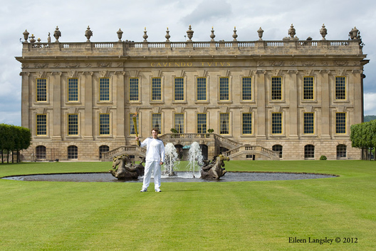 Local youth Ben Hope holds the Olympic Torch and Flame in front Chatsworth House in Derbyshire during the Torch Relay.