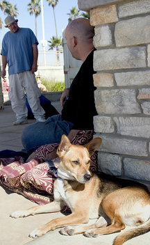 Homeless man Joshua of Los Angeles sits and talks with his friend Robert as his dog, Sparky, soaks up the sun and watches people walk by near the pier.