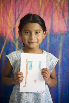 Olivia proudly holds up a drawing she drew for the children in Northfield, Minnesota.