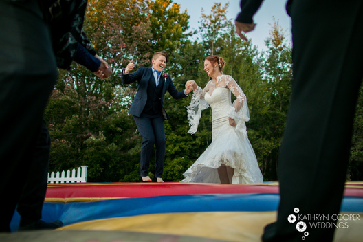 Married couple jumping on bounce pad or bouncy house for fun unique wedding lgbtq couple