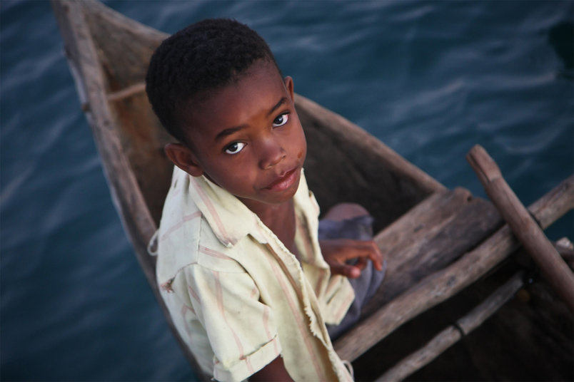 Portrait of a Malagasy child attempting to trade goods from his wooden pirogue.
