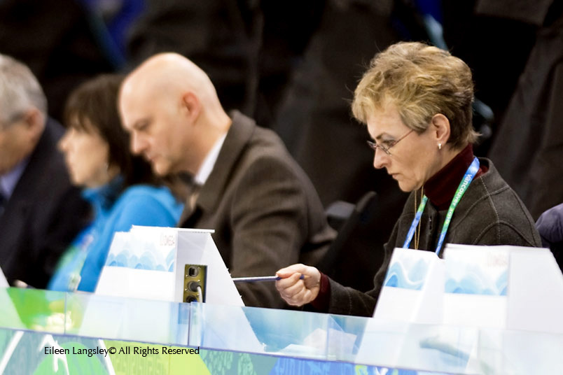 A portrait image of judges at the Figure Skating competition concentrating on thier assessment of a performance.