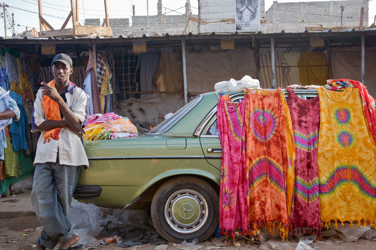 "Once back in Dakar, we visit the colorful Marché des HLM (""HLM Market""), with its long rows of market stalls (and cars) decorated with colorful fabrics for sale."