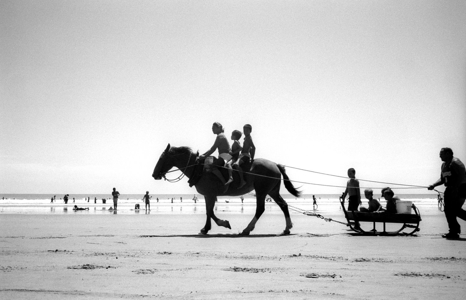 © Tamara Voninski. Ahipara, New Zealand. Maori children ride a horse and sleigh across the sand at the southern end of Ninety Mile Beach at Ahipara (North Island)  New Zealand. In Maori legend, the spirits of the dead depart the earth along this beach.  The New Zealand government had proposed laws to prevent Maori from claiming ownership of the coastline and seabed in New Zealand.