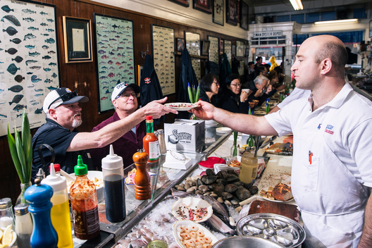 Kevin Sancimino, right, delivers a plate of Sicilian sashimi to Adam Braunstein and Joe Winograde during service at Swan Oyster Depot in San Francisco, Calif. on Tuesday, April 2, 2019.