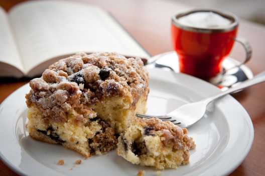 reading a book while eating a delicious bite of blueberry coffee cake with a shot of espresso in a demitase cup. Food photography by Chad Jackson