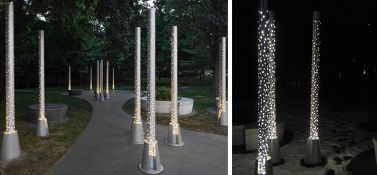 Custom laser cut anodized aluminum outdoor poles with cast aluminum base and integral signage, single LED light source