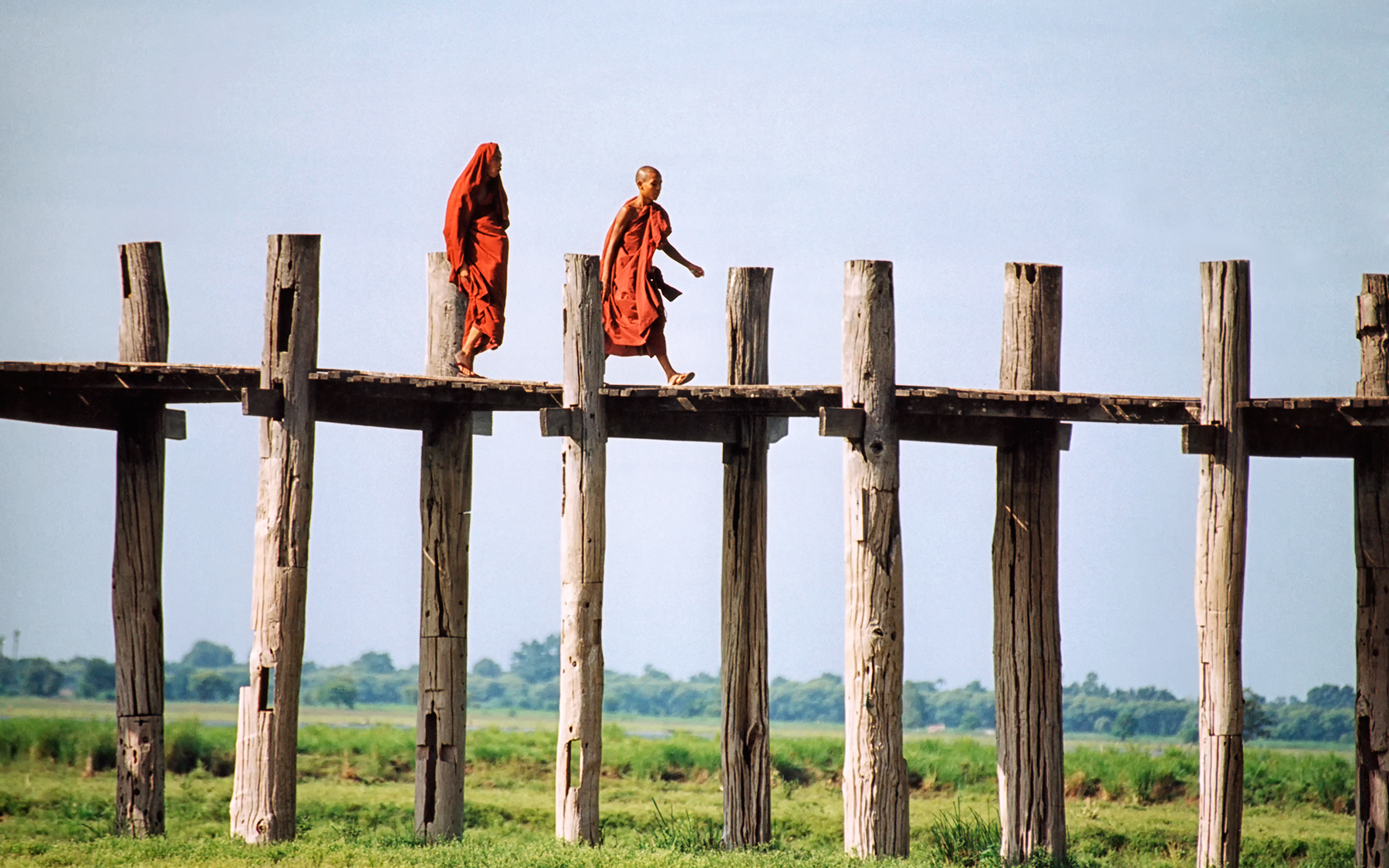 Buddhist monks walking across U bein's Bridge, Myanmar (Burma), Amarapura, near Mandalay. U bein's Bridge was built in 1850, crossing Lake Taungthaman; it is the longest teak wood bridge in the world (.75 miles or 1.2 kilometers long). The peaceful surroundings and beautiful scenery make it a wonderful place to sit, relax and watch life go by. Amarapura was a former capital of Myanmar (Burma).