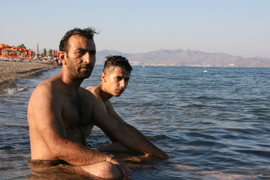 A Syrian refugee from Derzoor and his son enjoy a swim on one of Kos's beaches just one day after smuggling themselves onto the island by boat. The Turkish coast, where the two men set off from the day before, can be seen in the background.