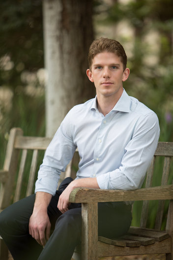Editorial portrait of Caucasian male sitting on bench in an outdoor setting by commercial photographer Nancy Rothstein