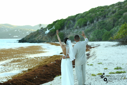 creative wedding photographer us virgin islands couple waving at helicopter on island