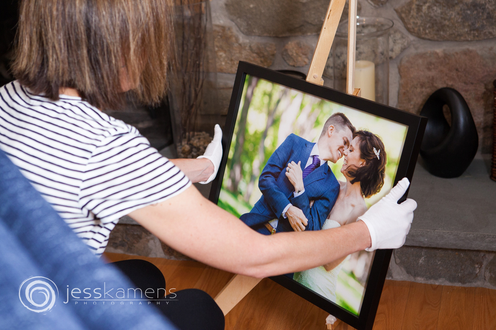 a bride admires her fine art archival wedding portrait from her wedding day in a black frame while touching it with gloves