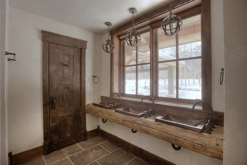 "With the possibility of sleeping so many people, this house needed a bathroom space capable of multiple handwashes at one time! Three sinks looking out to the wildlife and mountain views is highlighted by orbital wooden pendant lights above. A rustic wooden slab counter adds that unique ""chunk"" to the space."