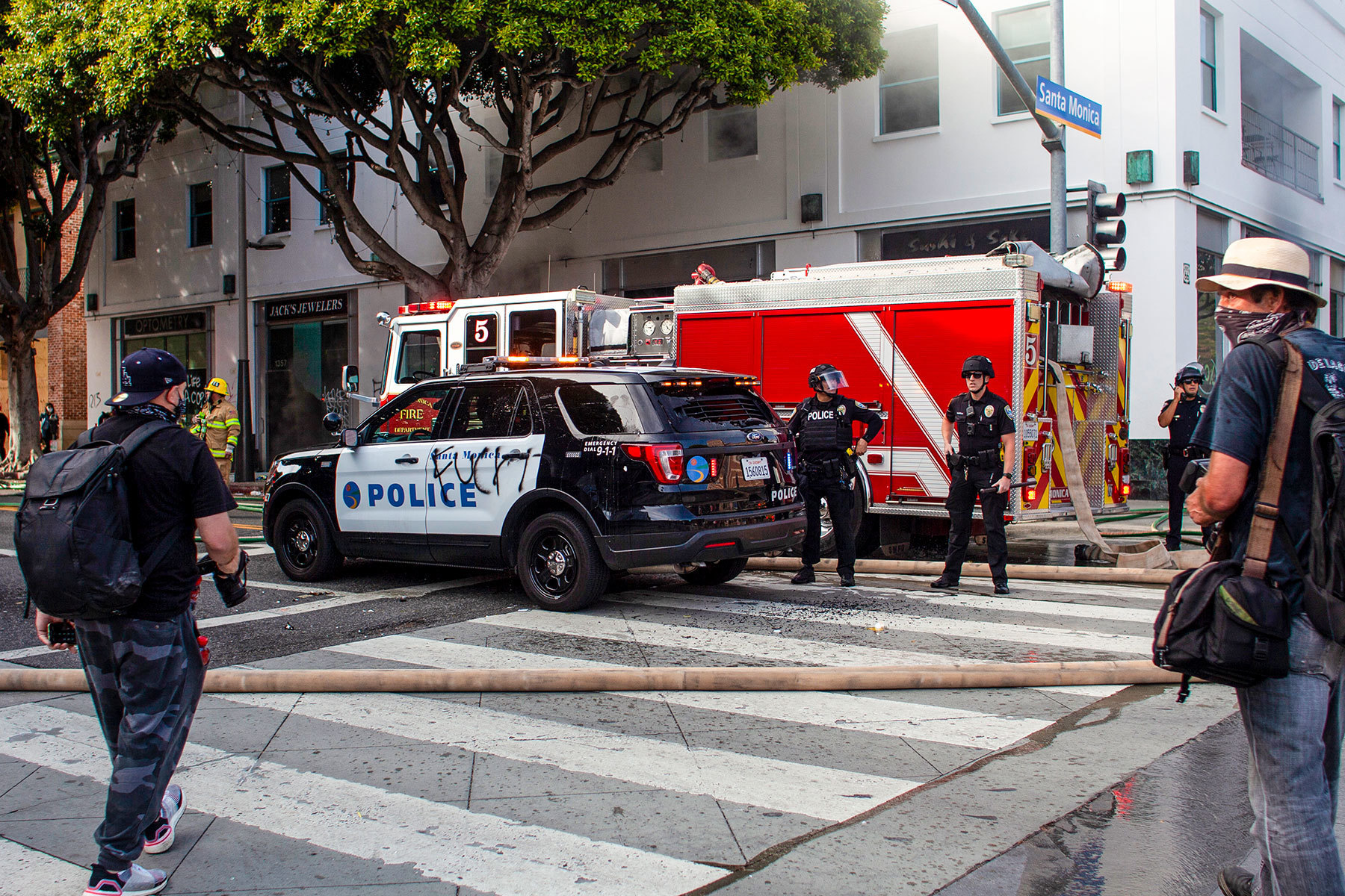 A Police cruiser is cornered by looters hurling missiles at the Police officers before backup arrives, Santa Monica, California Sunday, May 31, 2020. Corner of Santa Monica Blvd and 4th Street. The death of George Floyd, an African-American man in police custody, has ignited protests across the country.