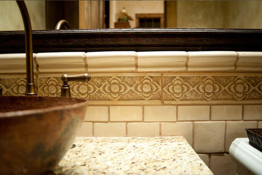 This copper sink and Bronze faucet play off the cream tile for a pleasing contrast.
