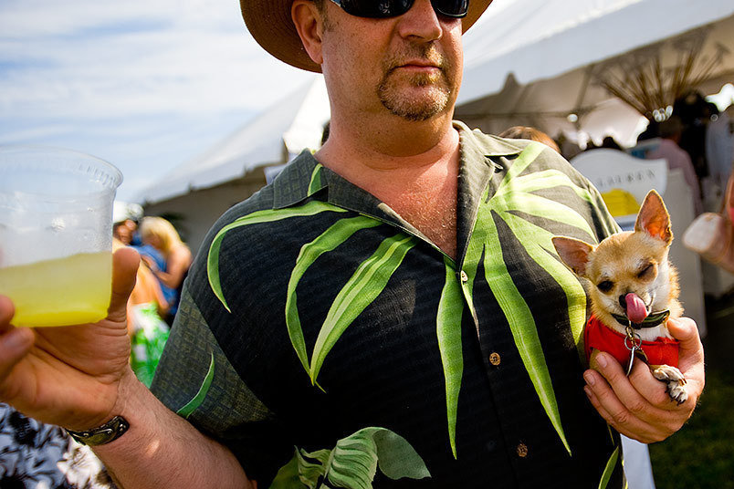 A man holds his drink and his dog at The Mercedes Benz Polo Challenge held at Two Trees Farm in Bridgehampton, NY