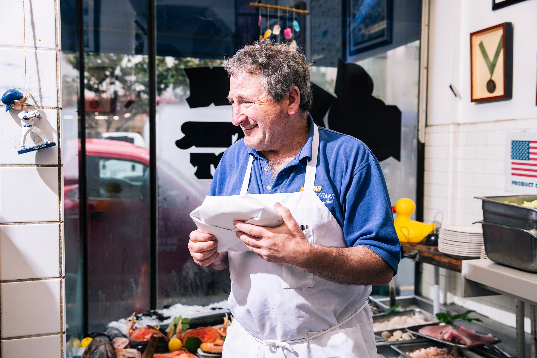 Tom Sancimino, center, smiles as he speaks with a long-time customer at Swan Oyster Depot in San Francisco, Calif. on Tuesday, April 2, 2019.