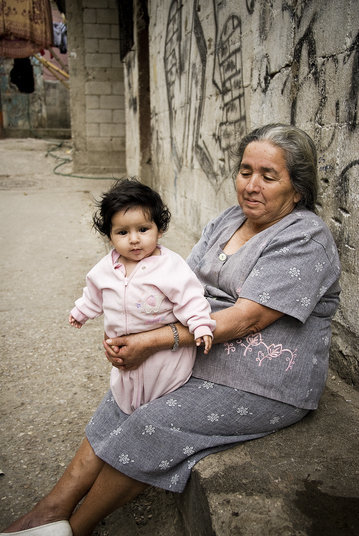 A proud grandmother holds her grandaughter in the alley with bullet holes in the wall behind her as reminders of the violence in her barrio.