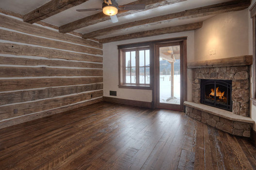 "A stone fireplace is nestled in the corner of this ""room with a view"". a wood chinked bed wall creates variety and wood beams continue the theme. The door opens to an outside private patio with panoramic mountain views. www.timberlineframers.com"
