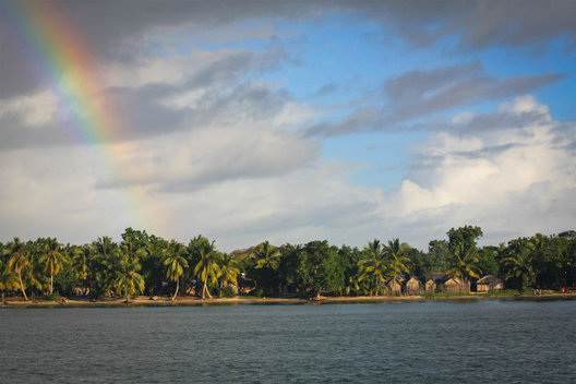 A rainbow appears over a small village on the East Coast of Madagascar.