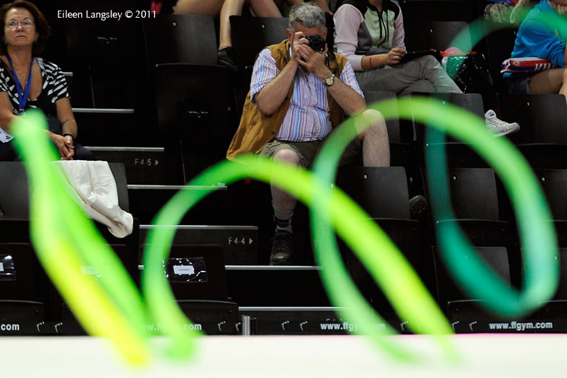A cropped generic image of a photographer in the audience photographing a gymnast competing with Ribbon at the World Rhythmic Gymnastics Championships in Montpellier.