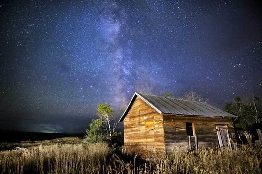 The Milky Way Galaxy wheels across the night sky with the Beartooth Mountains as a backdrop. A far-off thunderstorm drifts by to the south. An abandoned chicken coop slowly returns to the Earth. White Deer Ranch.