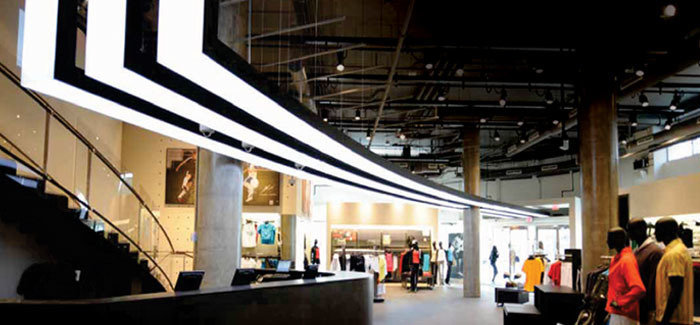Custom fabricated iconic adidas three strip logo light fixture running through flagship retail store and up front facade
