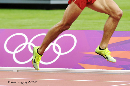 A cropped generic image of the legs of a runner racinbg past the Olympic rings on the track at the London 2012 Olympic Games.