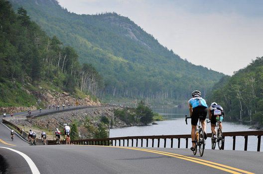 Triathletes make their way along a winding road in the 2009 Ironman Lake Placid Triathlon
