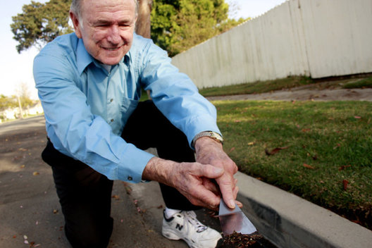 Dr. Jack Skinner scrapes up biofilm from the gutter that prompted his research.