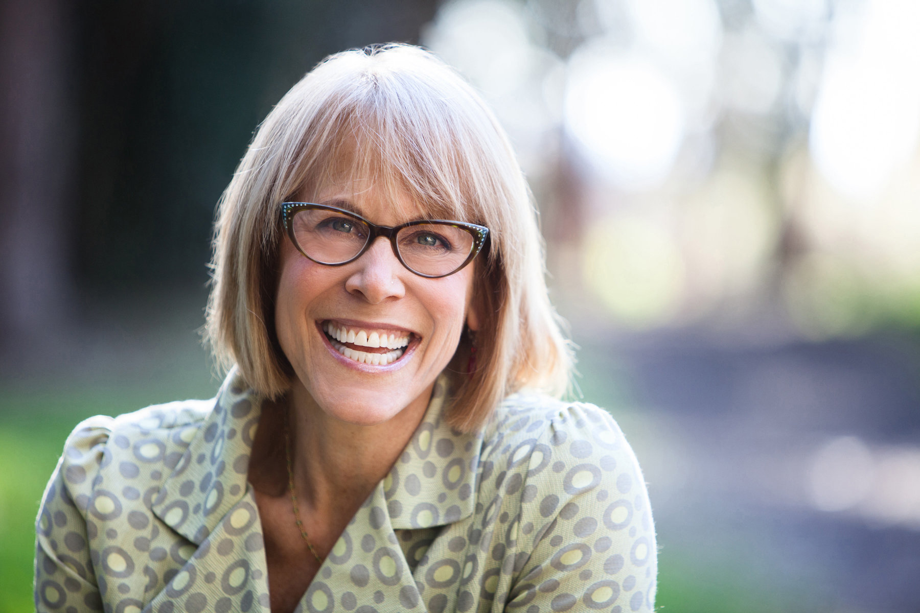 Editorial headshot of Caucasian blonde woman wearing glasses and smiling by commercial photographer Nancy Rothstein