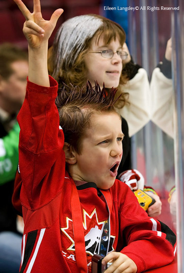 A young supporter cheers on the Canadian Women's Ice Hockey team during their match against Slovakia at the 2010 Winter Olympic Games in Vancouver.