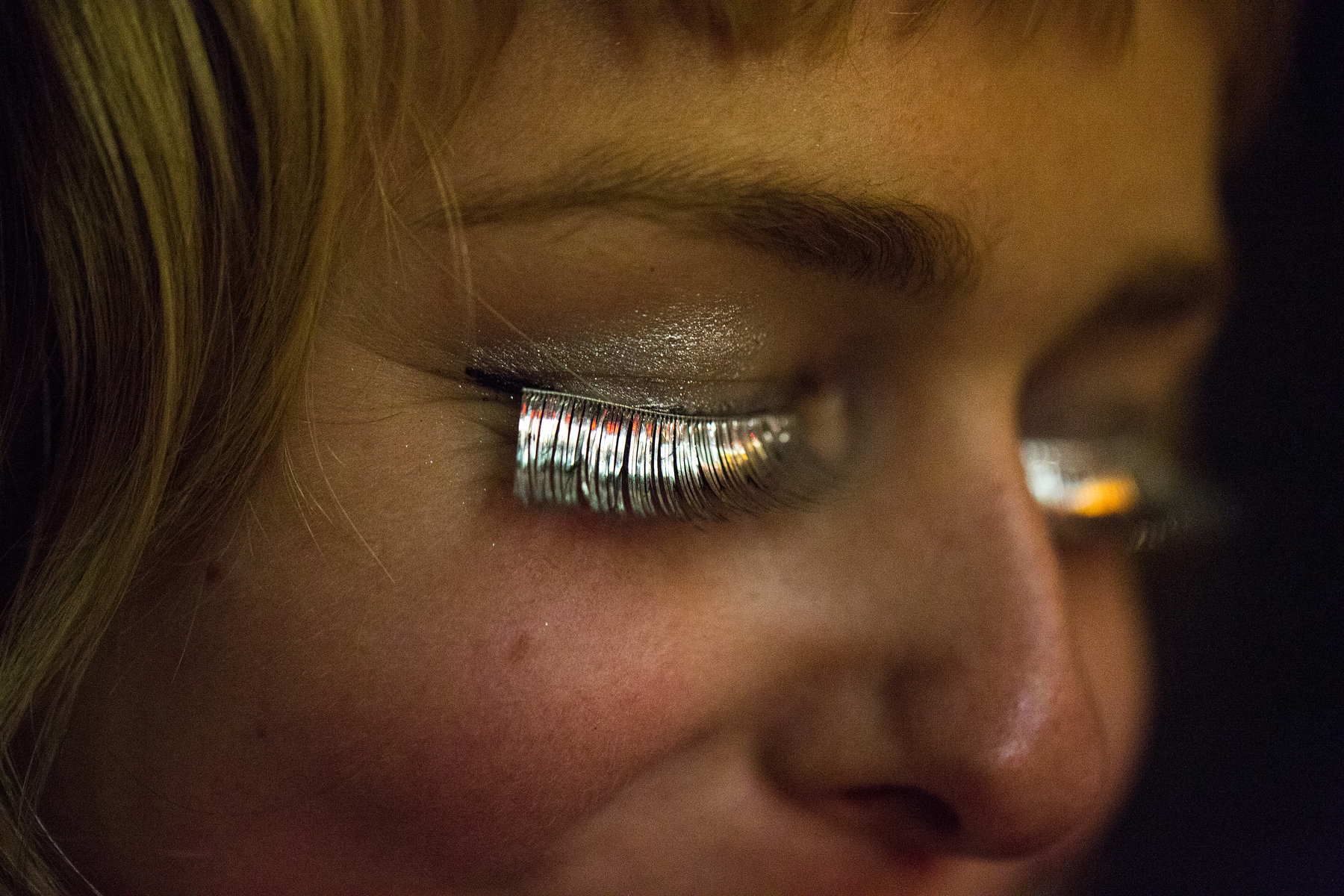 An exotic dancer is pictured wearing silver-colored eyelashes outside the Lusty Lady strip club in San Francisco, California September 1, 2013. United States' first and only unionized, employee-owned strip club shuts its doors on September 2 after its landlord refused to negotiate on a lower rent, local media reported.