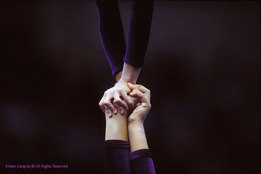 A generic close up image of the hands of two female sports acrobats in a supported handstand balance during competition.
