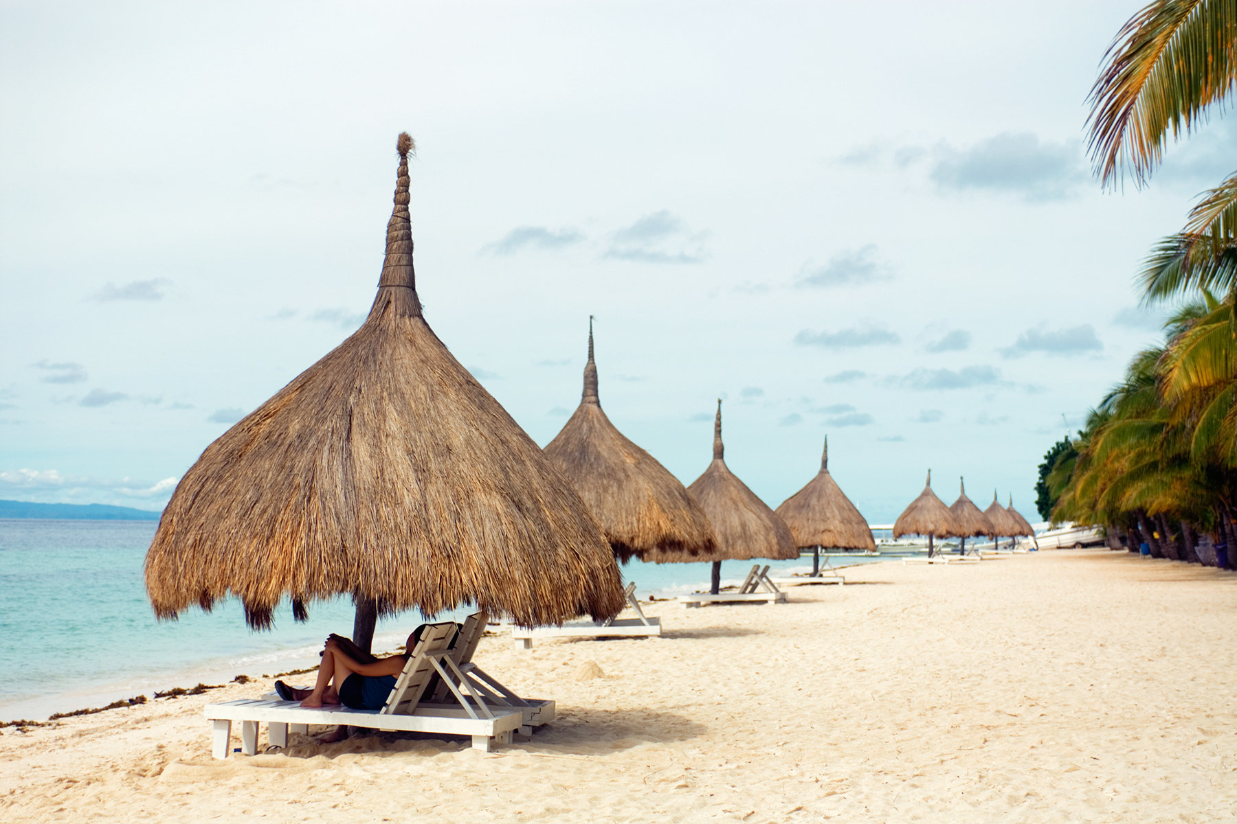 Philippines, People relaxing under thatched beach umbrellas, Bohol Beach Club, Alona Beach, Panglao Island, Visayas