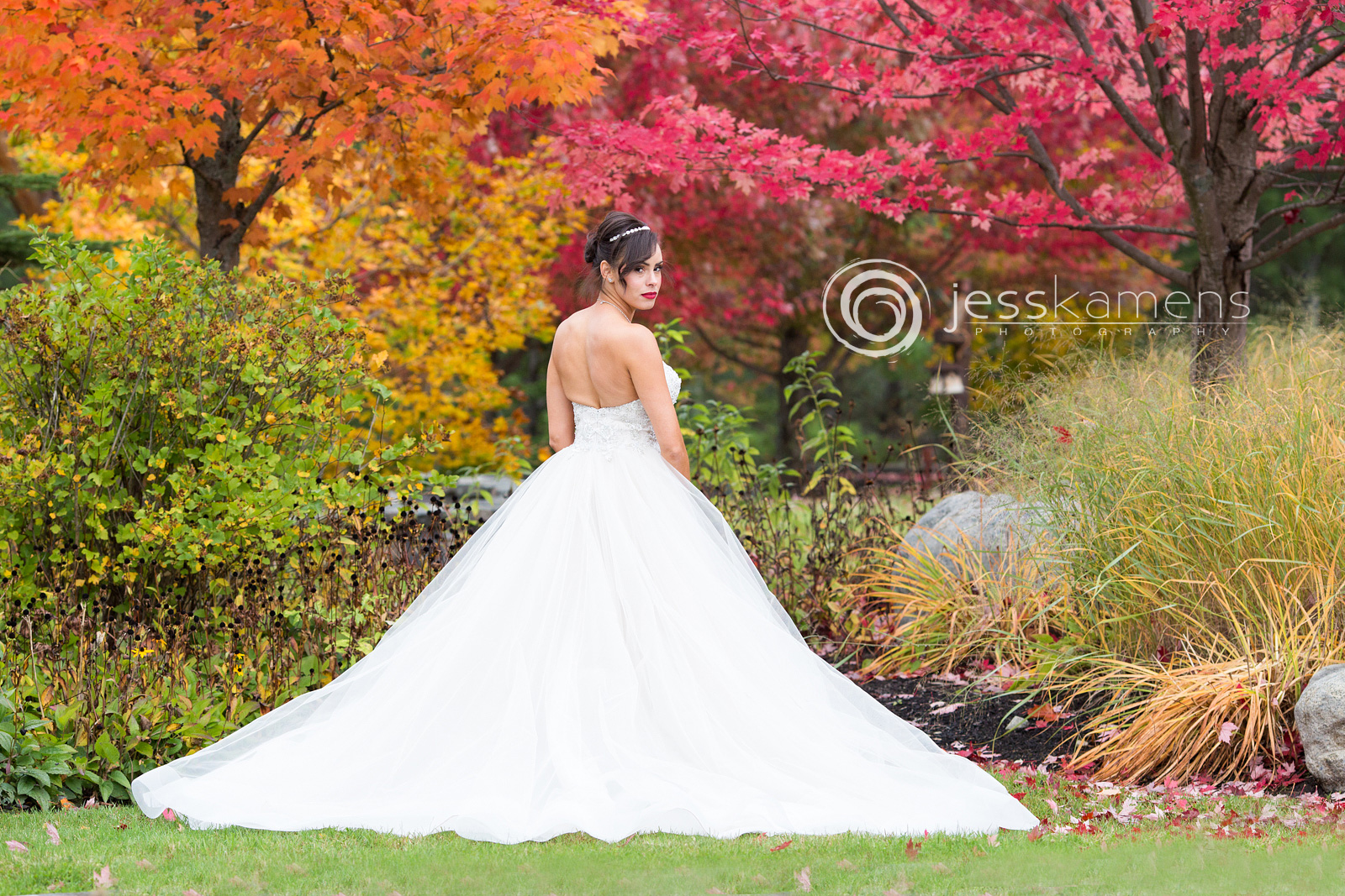 bride portrait of her standing in front of trees all different colors and her back is facing towards us