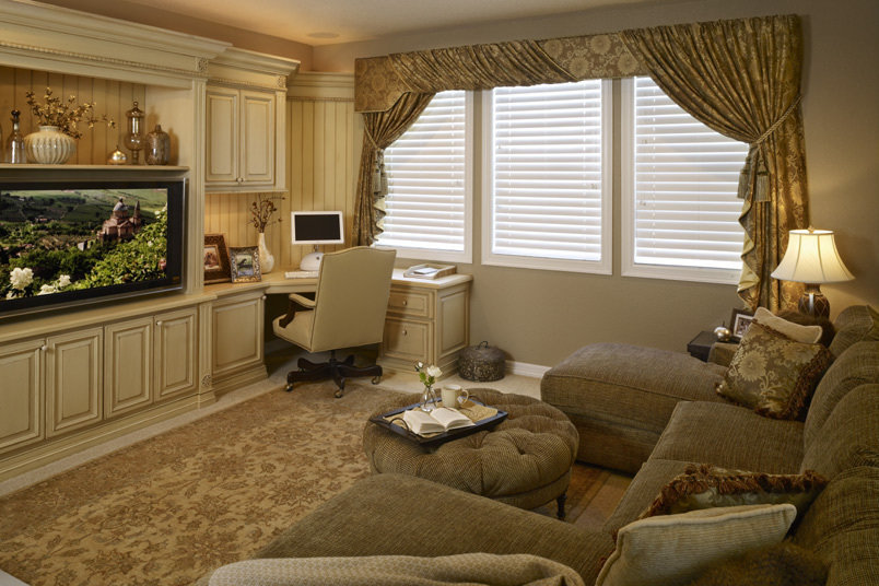An asymmetrical swagging window treatment of expensive floral silk combines both a hard upholsered cornice and soft draping panels. The sectional boasts not one but TWO chaise lounges to optomize loungability. The custom wall of cabinetry includes an entertainment space, a desk space and additional storage with a butter painted finish and chocolate glaze.