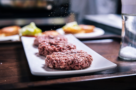 An Impossible burger patty is being seasoned at the test kitchen inside Impossible Foods headquarters in Redwood City, Calif. on Thursday, June 20, 2019.