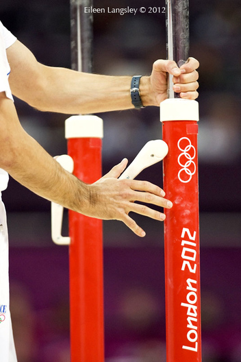 A coach adjusts the parallel bars during the Gymnastics competition at the 2012 London Olympic Games.